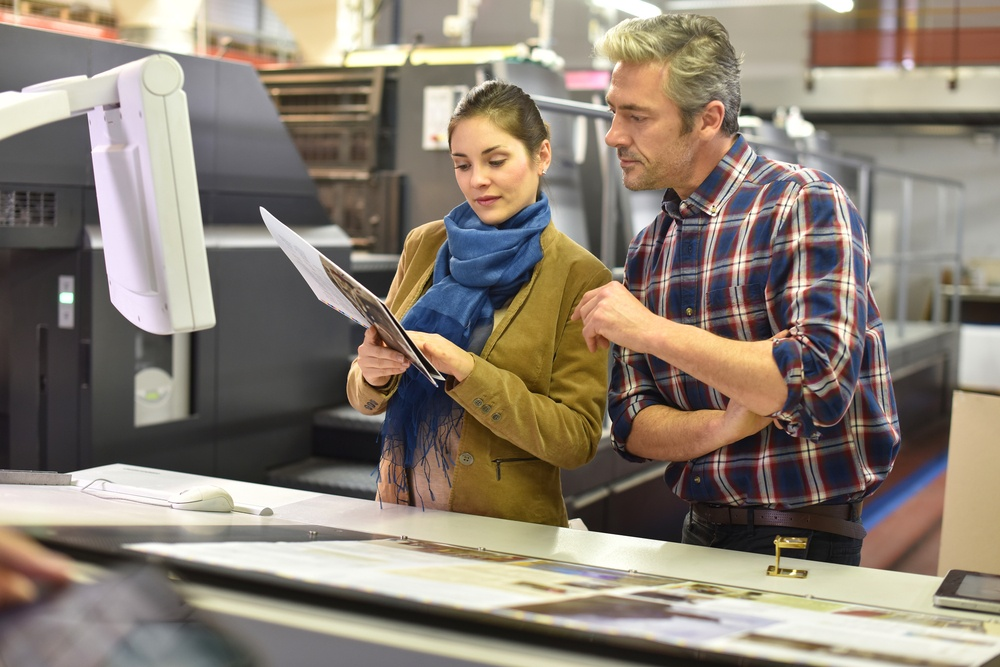 Man in printing company showing client print