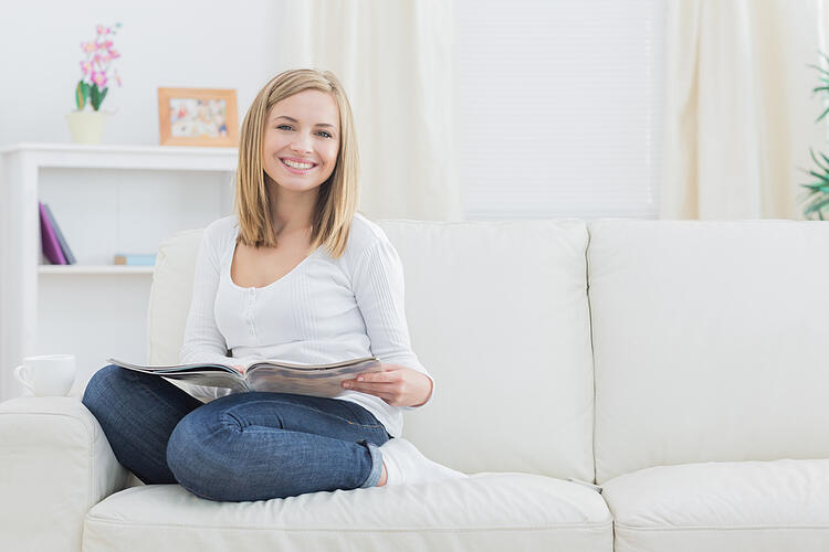 Portrait of happy young woman with magazine sitting on couch at home