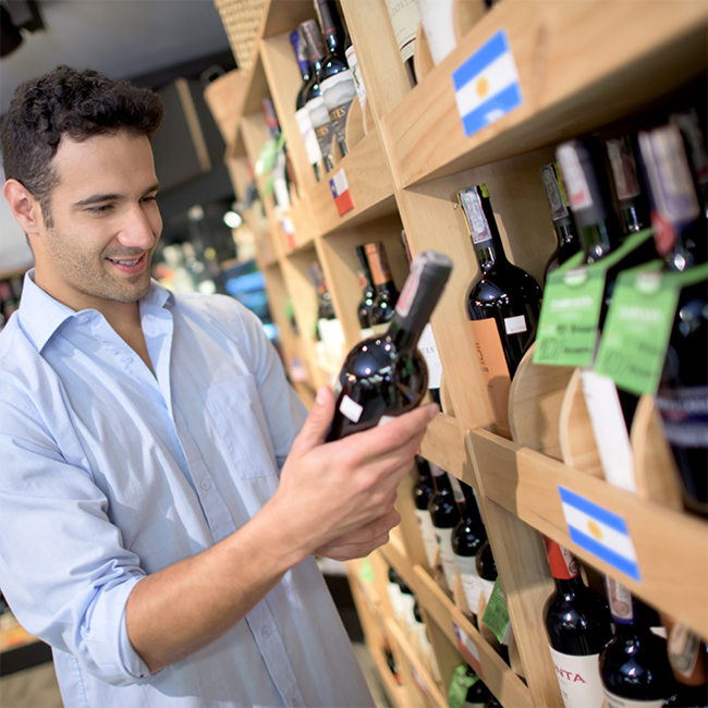 Man looking at wines at the supermarket cropped