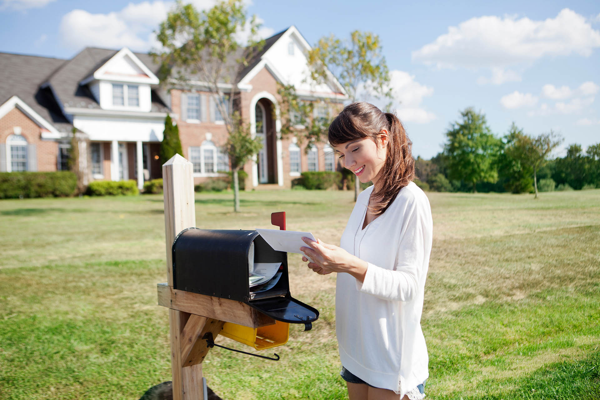 Woman examining direct mail delivered to her mailbox